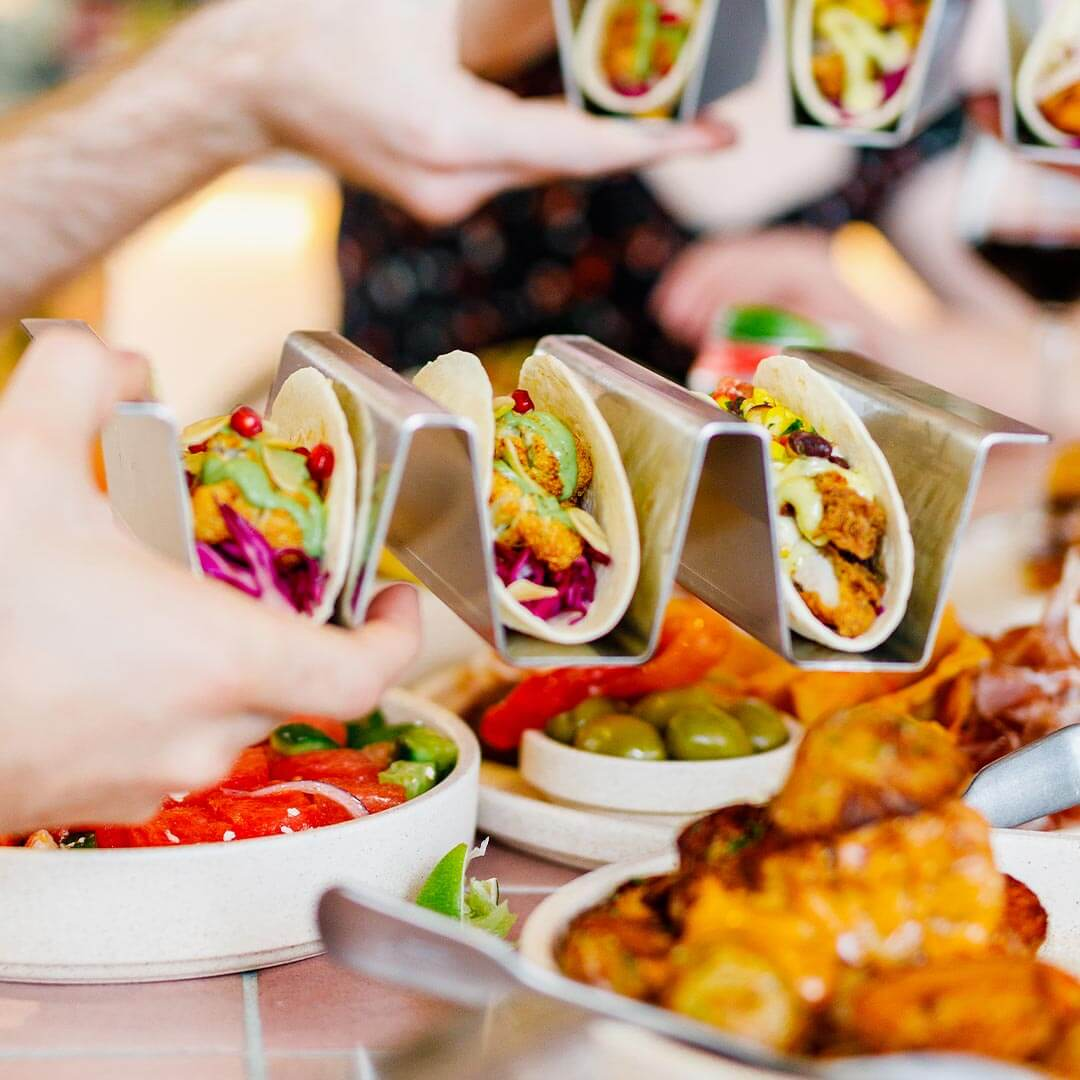 Tacos being passed over the table